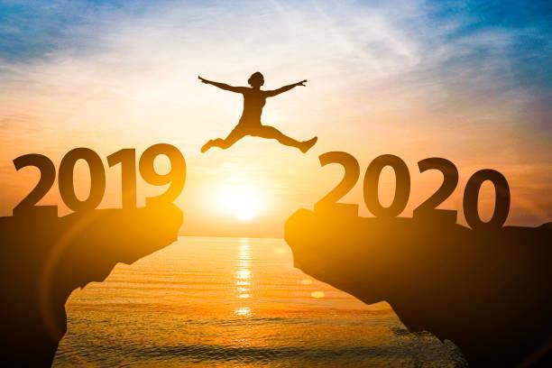 人間は2019年から2020年にジャンプします。新年のコンセプトの開始。 - 終わり ストックフォトと画像