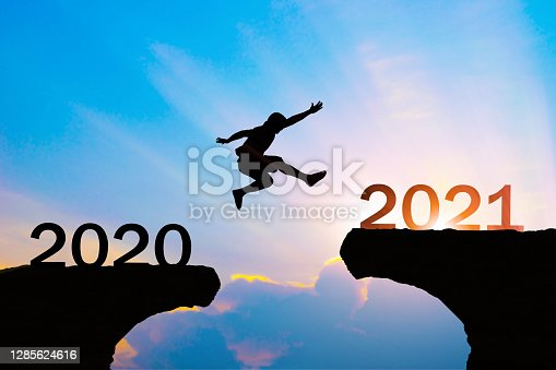 Man jump silhouette between year 2020 and 2021 new year concept.