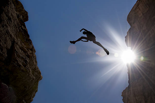 Man Jump through Gap in the Mountain stock photo