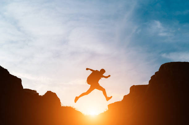 Man jump through gaps between hills stock photo