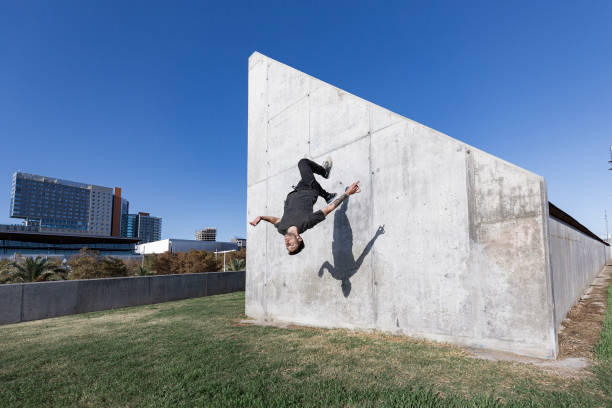 Man jumping and doing backflips while practicing parkour in the city stock photo