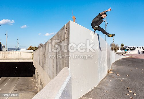 istock Man jumping and practicing parkour in the city 889068608