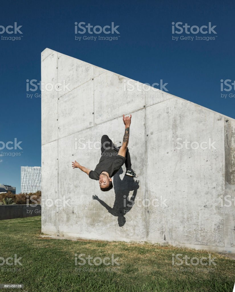 Man jumping and practicing parkour in the city stock photo