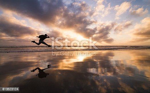 istock Man Jumping at beach. 613523124