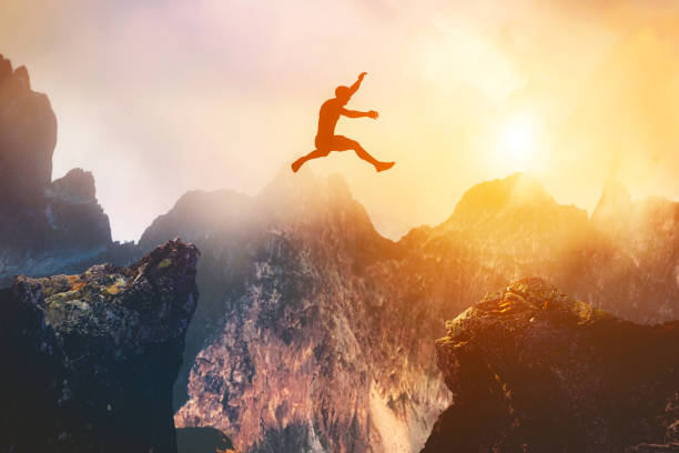 Man jumping between rocks. Overcome a problem for a better future stock photo