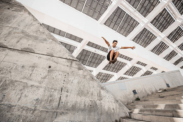 man jumping doing urban parkour - daredevil stock pictures, royalty-free photos & images