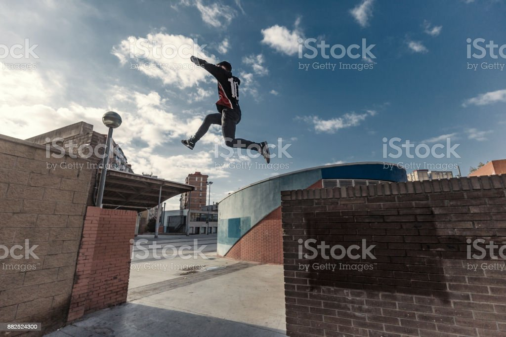 Young man practicing parkour in the city in Cornella de LLobregat...