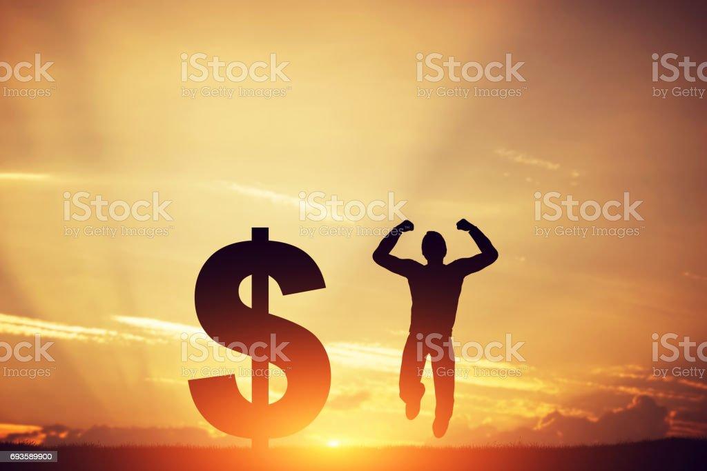 Man jumping for joy next to dollar symbol. Winner of lottery stock photo