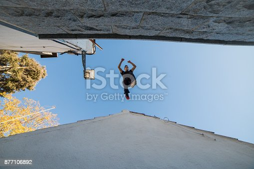 istock Man jumping from one roof to another 877106892