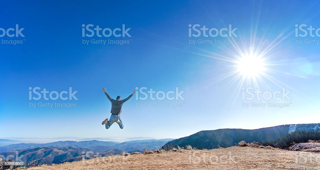 Man jumping high in the sky on a mountain view stock photo