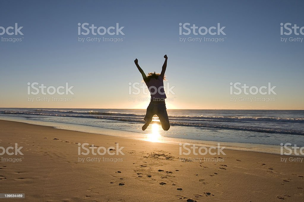 Man jumping high up at the beach during sunrise royalty-free stock photo