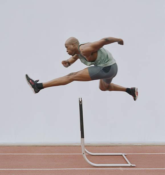 Homem pulando obstáculo, vista lateral - foto de acervo