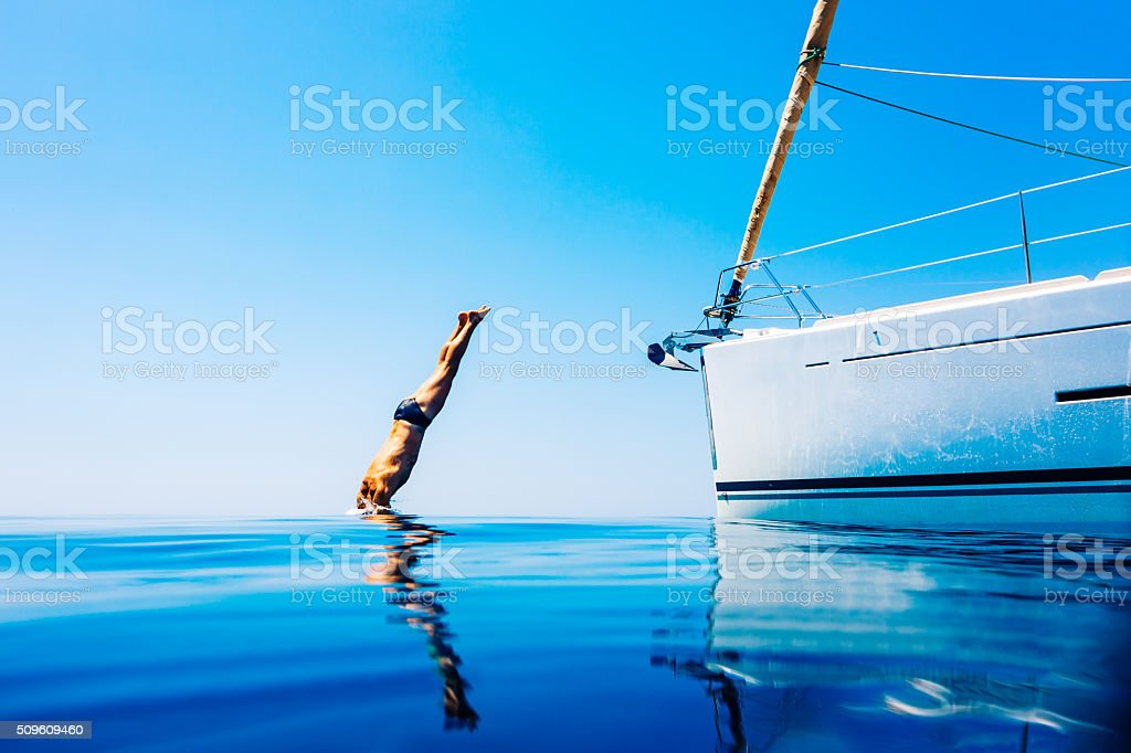 Man jumping in sea from sailboat stock photo