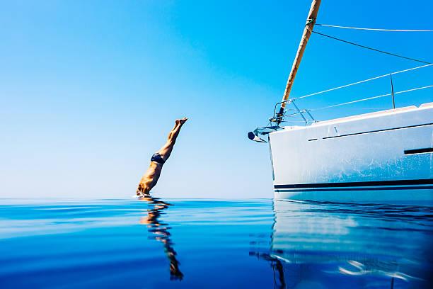 Salto de hombre en el mar desde la navegación a vela - foto de stock