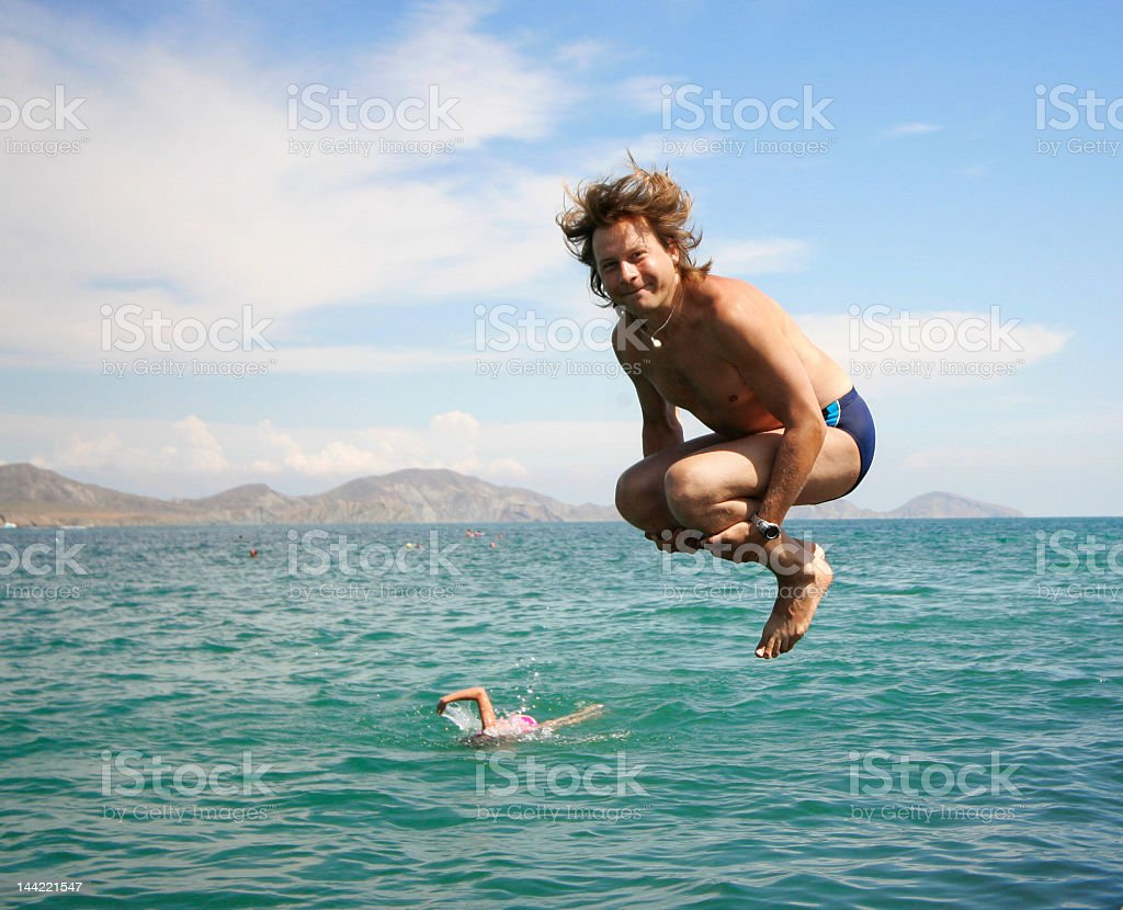 A man jumping in the ocean while someone swims stock photo