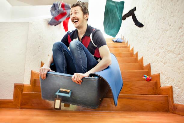 homme sauter à l'intérieur d'une valise de l'escalier - valise humour photos et images de collection
