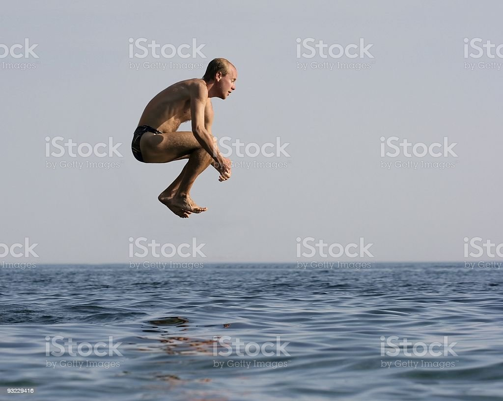 Man jumping into a large body of water royalty-free stock photo