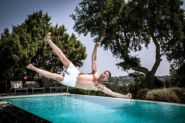 Man jumping into swimming pool stock photo