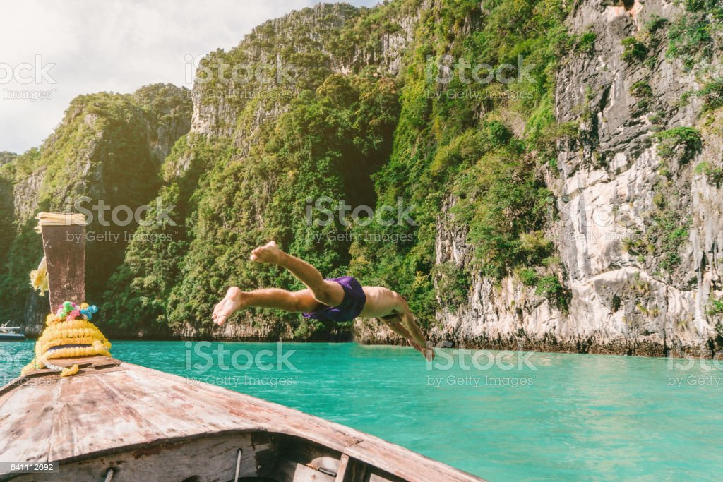 Man jumping into the water from Thai Taxi Boats stock photo