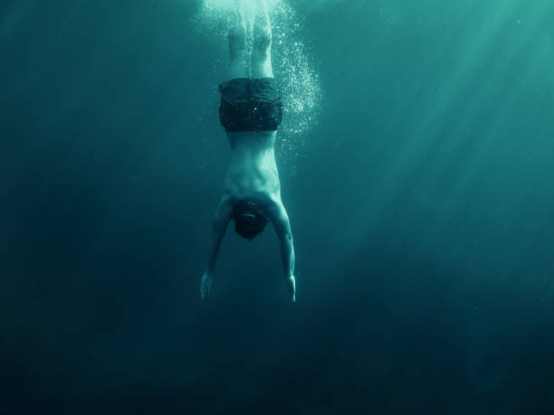 Man jumping into the water. Underwater shot. Vacation, sports and active lifestyle concept. Man jumping into the water. Underwater shot. Vacation, sports and active lifestyle concept. free diving stock pictures, royalty-free photos & images