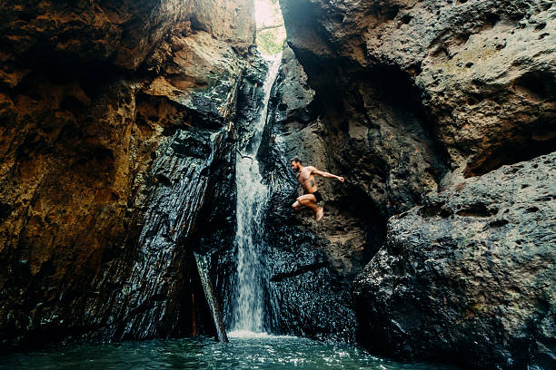 man jumping into tropical waterfall - waterfall stock photos and pictures