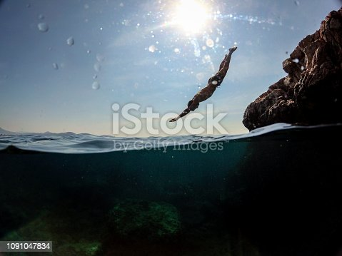 Man jumping into water from rocks WILD