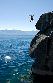 Man jumping off a cliff into the sea
