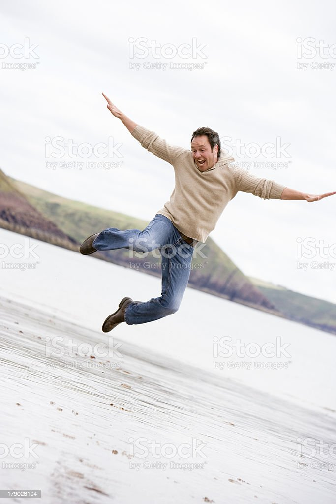 Man jumping on beach smiling royalty-free stock photo