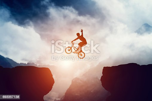 Man jumping on bmx bike over precipice in mountains at sunset. Raising hand showing hello gesture. Extreme sport, risk, cycling.