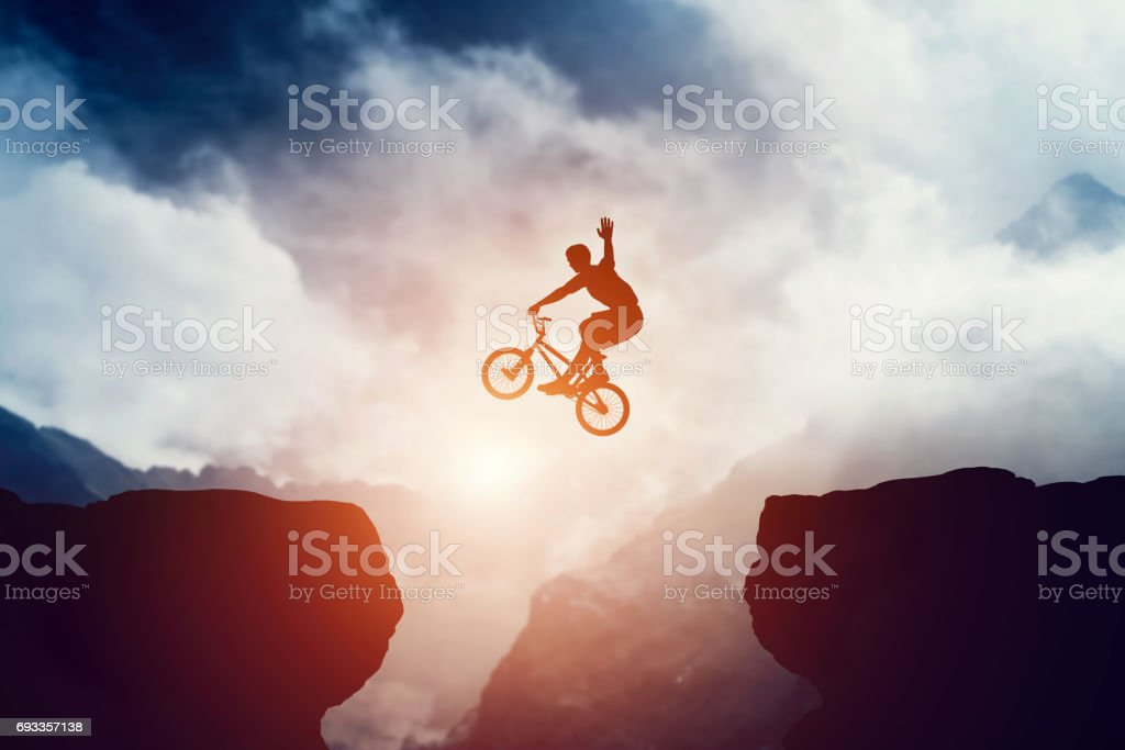 Man jumping on bmx bike over precipice in mountains at sunset. stock photo