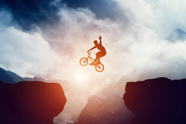 man jumping on bmx bike over precipice in mountains at sunset. - daredevil stock pictures, royalty-free photos & images