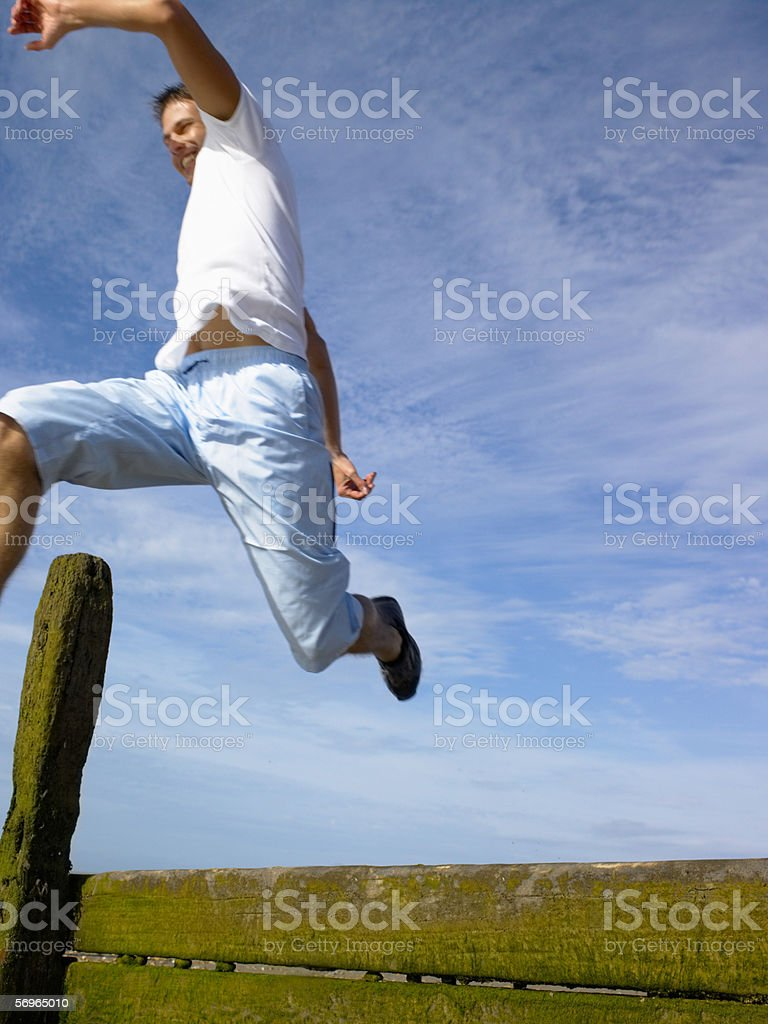 Man jumping over a fence royalty-free stock photo