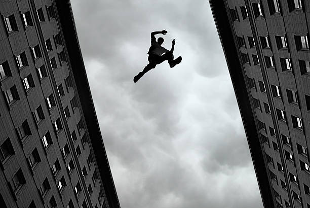 man jumping over building - daredevil stock pictures, royalty-free photos & images