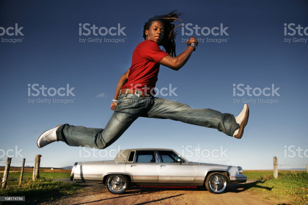 Man jumping over car stock photo
