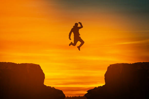 Man jumping over cliff on sunset background,Business concept idea stock photo