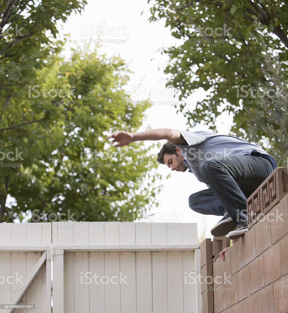 Man jumping over fence royalty free stockfoto