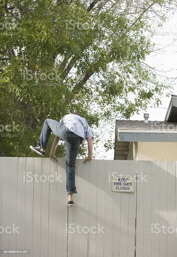 Man jumping over fence, rear view royalty-free stock photo