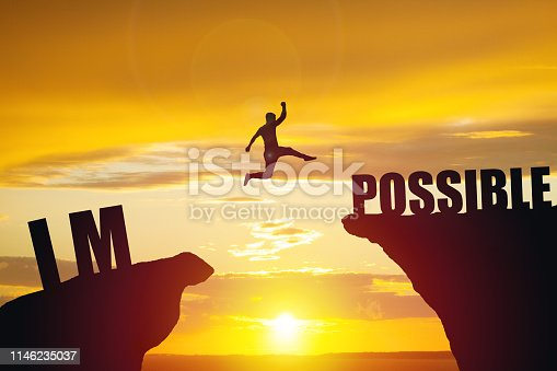 Man jumping over impossible or possible over cliff on sunset background. Business concept idea