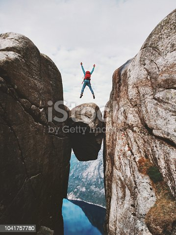 Man jumping over Kjeragbolten Travel in Norway Kjerag mountains extreme vacations adventure tourist happy emotions success concept