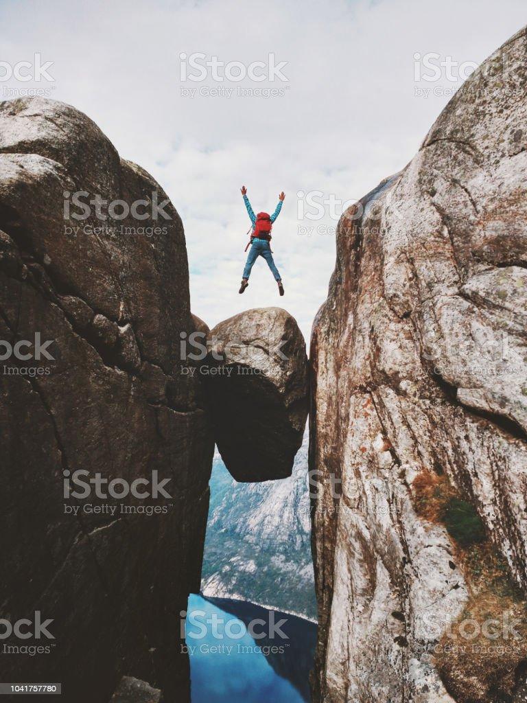Mann springt über Kjeragbolten Reisen in Norwegen Kjerag Bergen extreme Urlaub Abenteuer Touristen glücklich Emotionen Erfolgskonzept – Foto