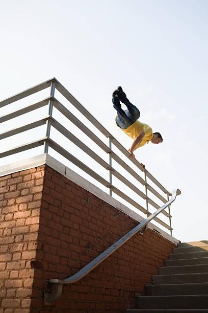 ein mann springen über haltestangen - parkour stock-fotos und bilder