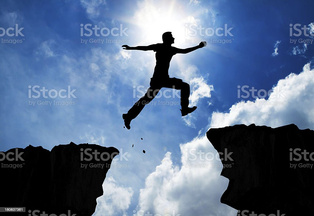 Man jumping over the mountains stock photo