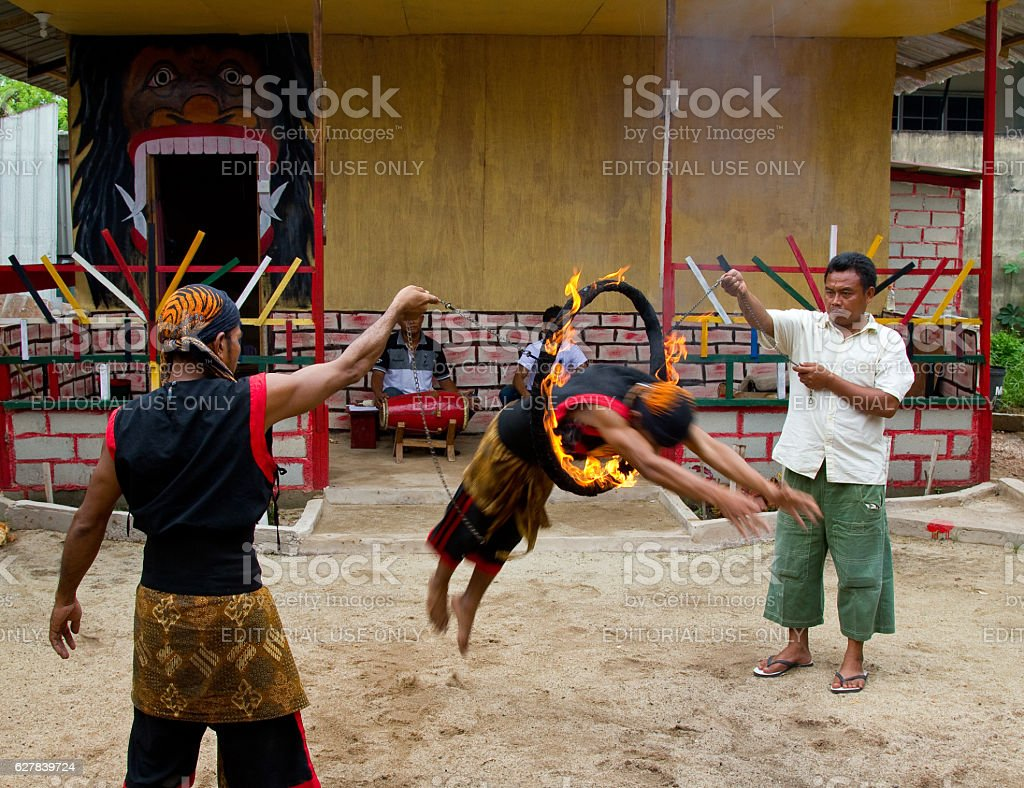 Man jumping through a fire ring wearing traditional attire stock photo