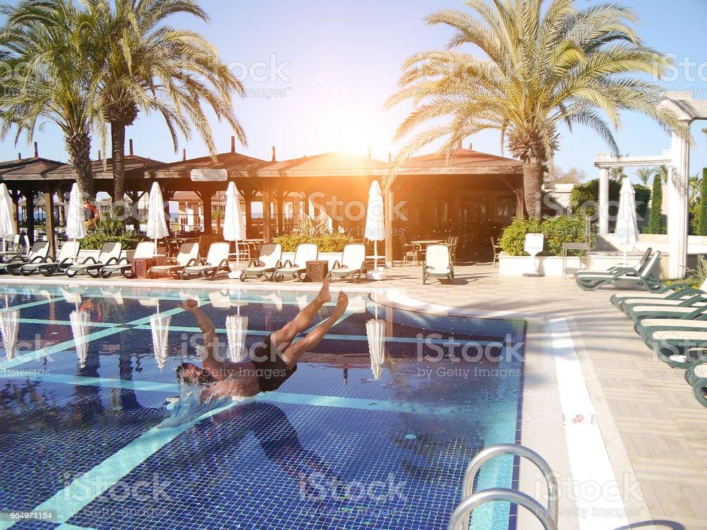 Mann springt, Hotel Schwimmbad Sommer Ort Seitenansicht – Foto