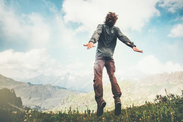Mann sprang auf Berge in Wolken Himmel Lifestyle Reisen emotionale Euphorie Erfolg Konzept Abenteuer Sommerurlaub im freien – Foto