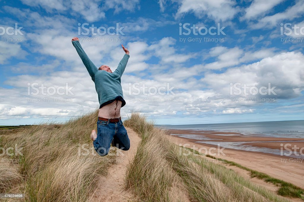 man jumping victoriously stock photo