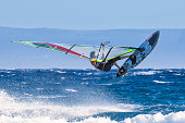 Windsurfer riding waves and jumping