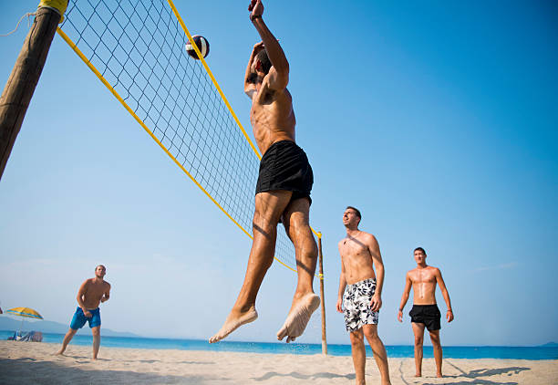 Man jumping while playing beach volleyball stock photo