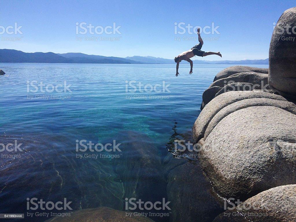 Man jumping wildly into Lake Tahoe stock photo