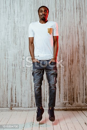 664626542 istock photo Man jumping with hands in pockets 1015304700